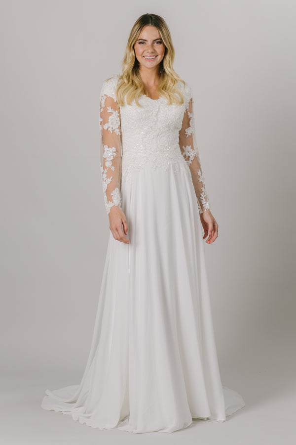 This a-line modest wedding dress is the perfect combination of lace and sparkle. It has a lovely v-neck and illusion long sleeves with buttons up the cuff.  Shown in Ivory/Nude.