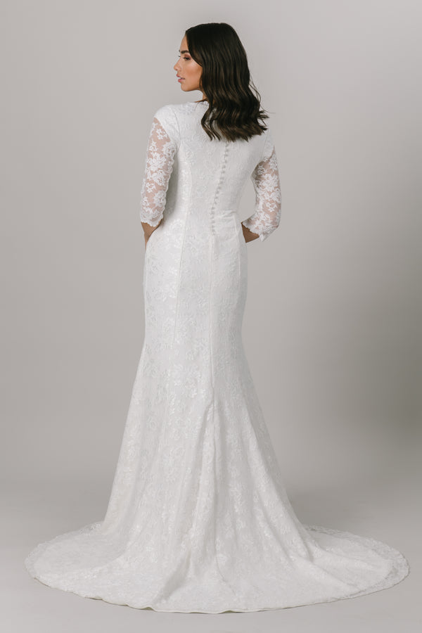 This fitted modest wedding dress features a dainty lace pattern, fun illusion half-sleeves and an adorable ruffled v-neckline. Available in Ivory (as pictured) and Ivory/Cappuccino.  Style Love: This dress is part of our brand new, exclusive LatterDayBride wedding dress collection. From a bridal shop in Salt Lake City called LatterDayBride.