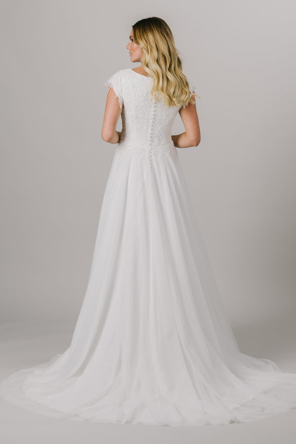 This a-line modest wedding dress features the most unique beading throughout the bodice. This lightweight and flowy gown features a boat neckline and gorgeous short sleeves.   Style Love: This dress is part of our brand new, exclusive LatterDayBride wedding dress collection. The back view of the dress from a bridal store in SLC, Utah.