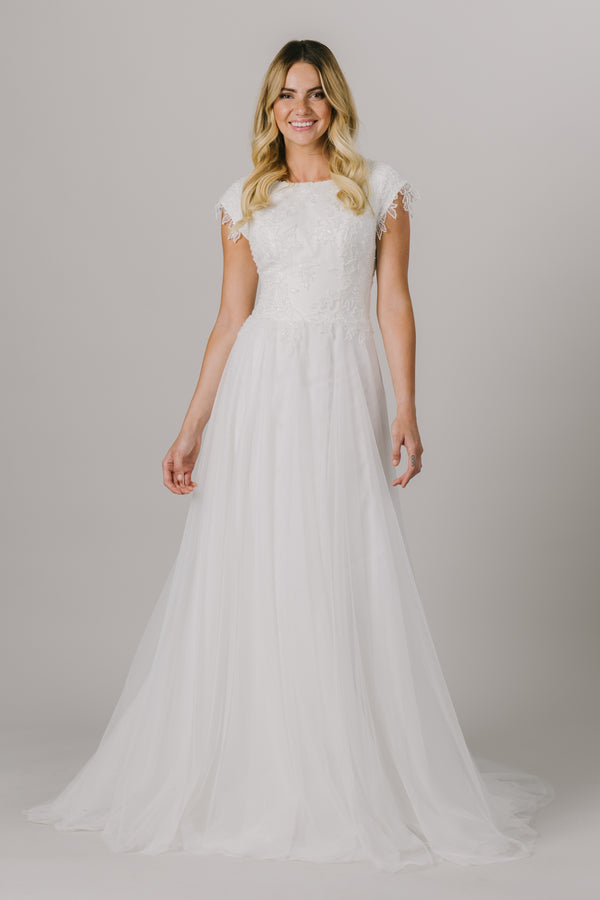 This a-line modest wedding dress features the most unique beading throughout the bodice. This lightweight and flowy gown features a boat neckline and gorgeous short sleeves.   Style Love: This dress is part of our brand new, exclusive LatterDayBride wedding dress collection.