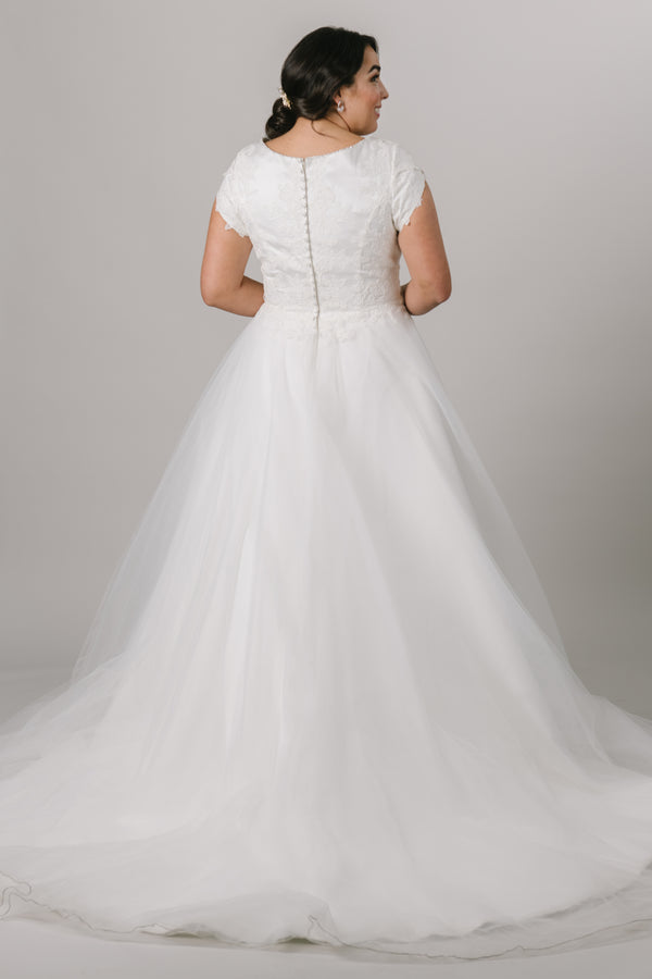 This elegant modest wedding dress is perfect for the traditional bride! We love the soft petal sleeves, the wide boat neckline, and the flattering cinched waist. The gown is shown in Ivory.  Style Love: Add a simple belt to add more sparkle to this gown or keep it simple as is! Feeling like a princess? Add a tiara to complete the look! From a Bridal store in downtown SLC,Utah.