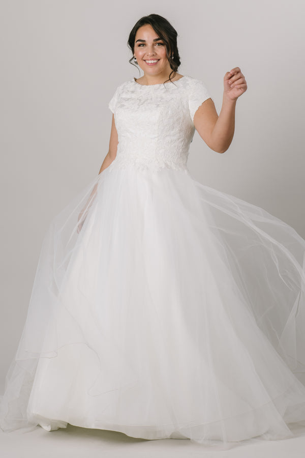 This elegant modest wedding dress is perfect for the traditional bride! We love the soft petal sleeves, the wide boat neckline, and the flattering cinched waist. The gown is shown in Ivory.  Style Love: Add a simple belt to add more sparkle to this gown or keep it simple as is! Feeling like a princess? Add a tiara to complete the look!