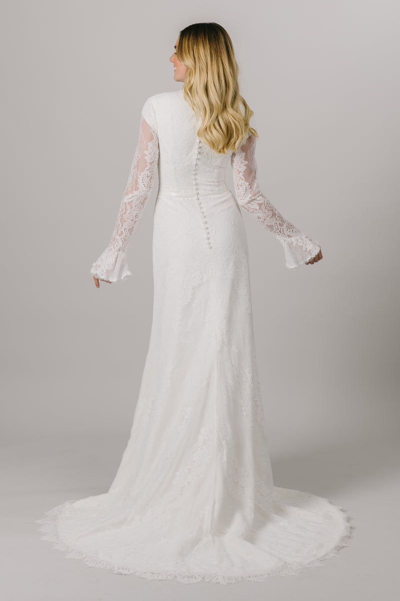 This unique modest wedding dress features a high neckline, some little bell sleeves and a gorgeous sequin belt. This a-line gown offers a dainty, delicate lace pattern. Available in Ivory and Ivory/Cappuccino.  Style Love: This dress is part of our brand new, exclusive LatterDayBride wedding dress collection.