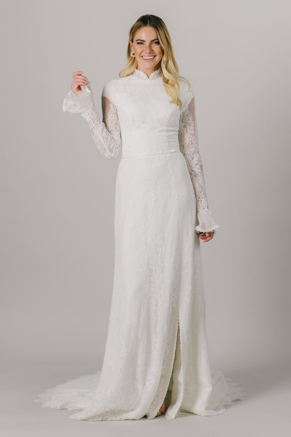 This unique modest wedding dress features a high neckline, some little bell sleeves and a gorgeous sequin belt. This a-line gown offers a dainty, delicate lace pattern. Available in Ivory and Ivory/Cappuccino.  Style Love: This dress is part of our brand new, exclusive LatterDayBride wedding dress collection. From a bridal shop in downtown Salt Lake City called LatterDayBride.