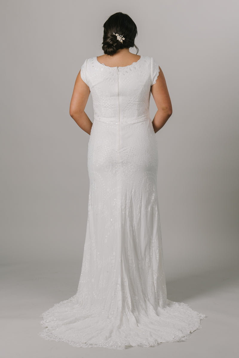 This fitted modest wedding dress is an amazing mixture of form and function! It features a shimmering lace pattern, a v-neckline and fun lace detailing on the sleeves.  Style Love: Although this gown is fitted, you will still be able to dance all night!  This listing includes all of the sizes we have currently available in our showroom in Downtown Salt Lake City. These gowns can be shipped out within one week. Plus size available in the store.