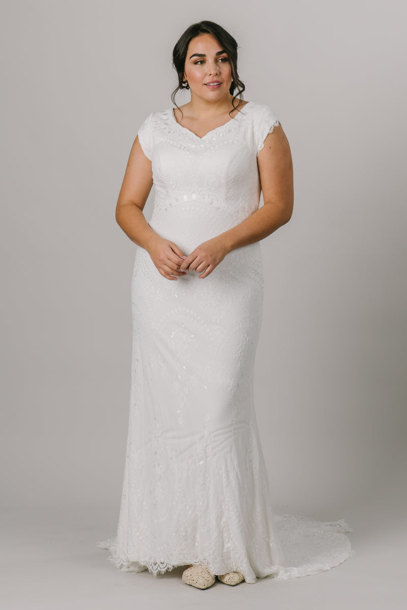 This fitted modest wedding dress is an amazing mixture of form and function! It features a shimmering lace pattern, a v-neckline and fun lace detailing on the sleeves.  Style Love: Although this gown is fitted, you will still be able to dance all night!