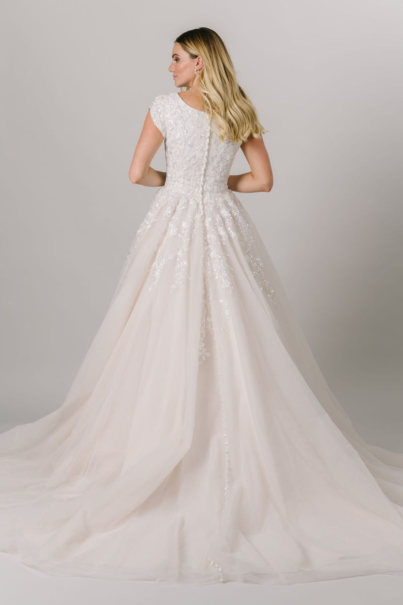This glamorous modest wedding dress screams princess. From the v neck to the sparkle bodice to the poof in the skirt, this gown is sure to put jaws on the floor. From LatterDayBride in downtown Salt Lake City.