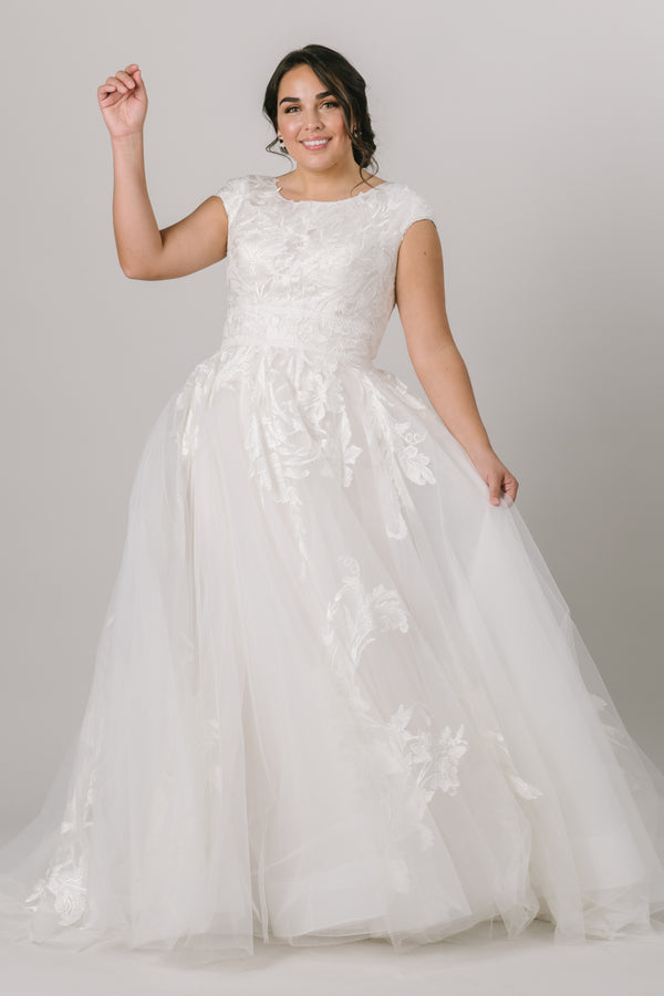 This modest wedding dress features touches of lace that trickle around the shirt and train giving it a simple yet elegant look! It's micro cap sleeves are modest yet modern.   Gown is available in Ivory/Platinum or Desert/Ivory (pictured)   Desert/Ivory sample available in store. Plus size available in store.  Style Love: We love this sophisticated take on the classic ballgown!
