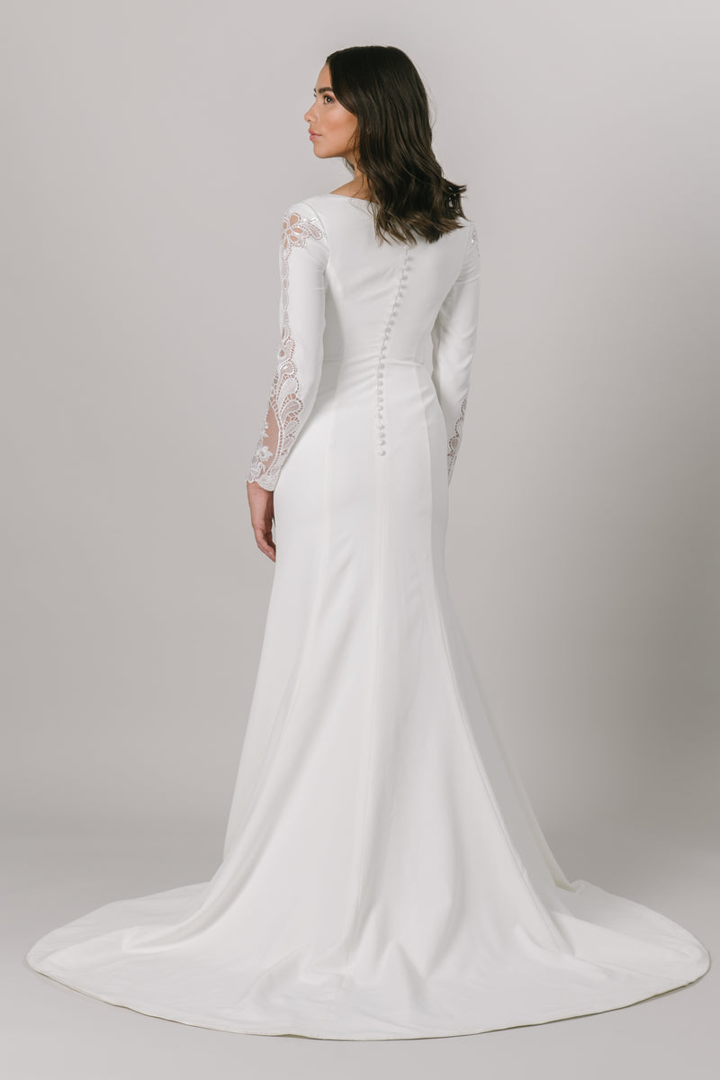 For all of our vivacious and fun brides, this modest wedding dress is for you. This fitted gown features long sleeves and a v-neckline. The otherwise simple dress has a gorgeous lace detail down the sides of the sleeves.  Style Love: This dress is part of our brand new, exclusive LatterDayBride wedding dress collection.