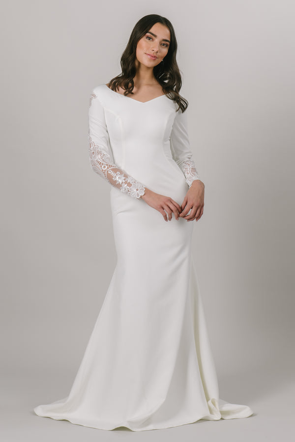 For all of our vivacious and fun brides, this modest wedding dress is for you. This fitted gown features long sleeves and a v-neckline. The otherwise simple dress has a gorgeous lace detail down the sides of the sleeves.