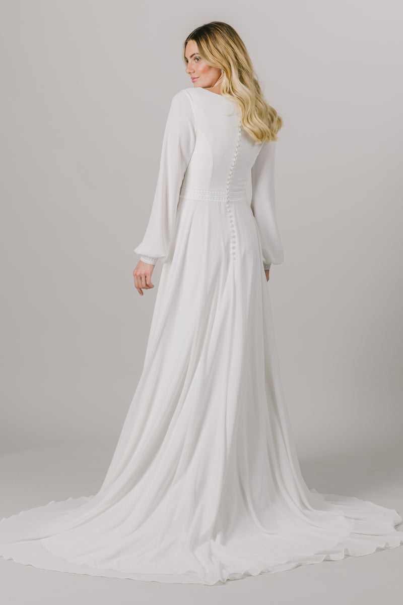 A long sleeve dream, this modest wedding dress is the perfect mixture of style and sophistication. This dress features a small belt around the waistline, a scoop neckline and bishop sleeves.  Style Love: This dress is part of our brand new, exclusive LatterDayBride wedding dress collection. The Back of the dress from a bridal store in downtown, SLC, Utah.