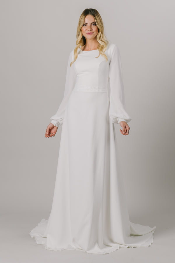 A long sleeve dream, this modest wedding dress is the perfect mixture of style and sophistication. This dress features a small belt around the waistline, a scoop neckline and bishop sleeves.  Style Love: This dress is part of our brand new, exclusive LatterDayBride wedding dress collection.
