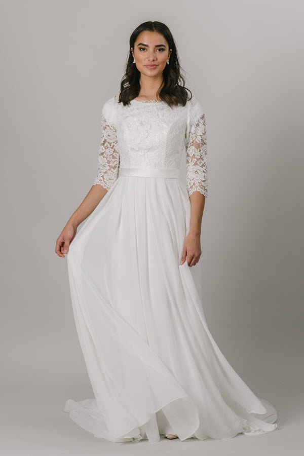 This classic modest wedding dress has everything you could want! Lace top, simple bottom, with 3/4 sleeve! The illusion sleeves, flattering waistband, and the pleated chiffon skirt make for the perfect dress. Almost a long sleeve with 3/4 sleeves. The gown is shown in ivory but is also available in white. Plus size available in the store.  Style Love: This gown has the perfect mix of everything! It's so flattering on everyone, and at this price, it's a total steal!