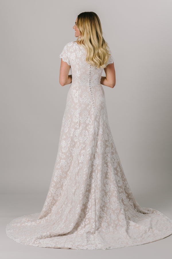 This fitted modest wedding dress is made with a delicate lace pattern and features a fun lace belt. The short illusion sleeves and neckline have the cutest little ruffle. Available in Ivory and Ivory/Cappuccino (as pictured).   Style Love: This dress is part of our brand new, exclusive LatterDayBride wedding dress collection. From A bridal store located in dowtown SLC,Utah.