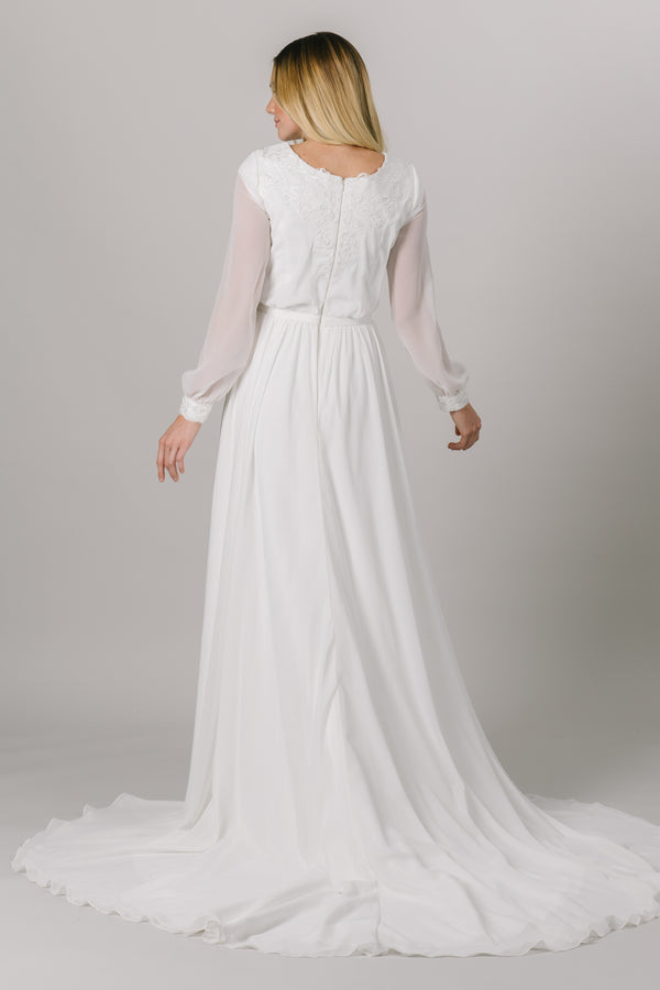 This long-sleeve modest wedding dress features a v-neckline, bishop sleeves, and an a-line fit that flatters every figure.   Style Love: Gorgeous shimmering lace around the neckline and sleeve cuffs! From a bridal store in downtown SLC, Utah.