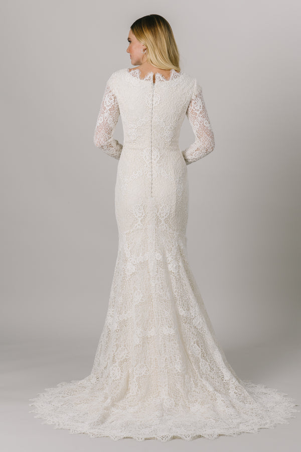This fit-and-flare, modest wedding dress features full lace, long sleeves and a high, scoop neckline. The full length sleeves are complete with thumb holes.   Style Love: Crystal buttons down the back add a gorgeous sparkle! From LatterDayBride weddings and occasions in downtown Salt Lake City.