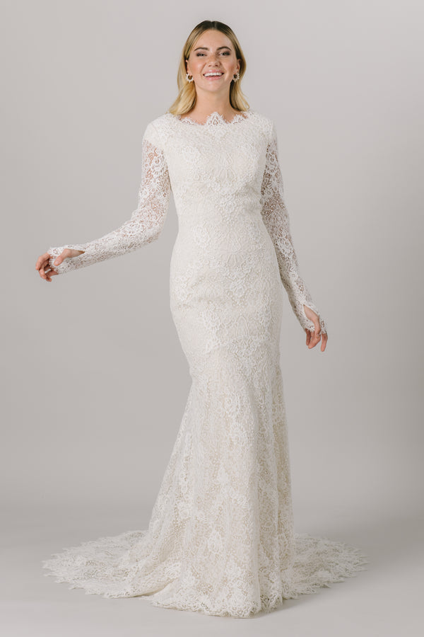 This fit-and-flare, modest wedding dress features full lace, long sleeves and a high, scoop neckline. The full length sleeves are complete with thumb holes.   Style Love: Crystal buttons down the back add a gorgeous sparkle!