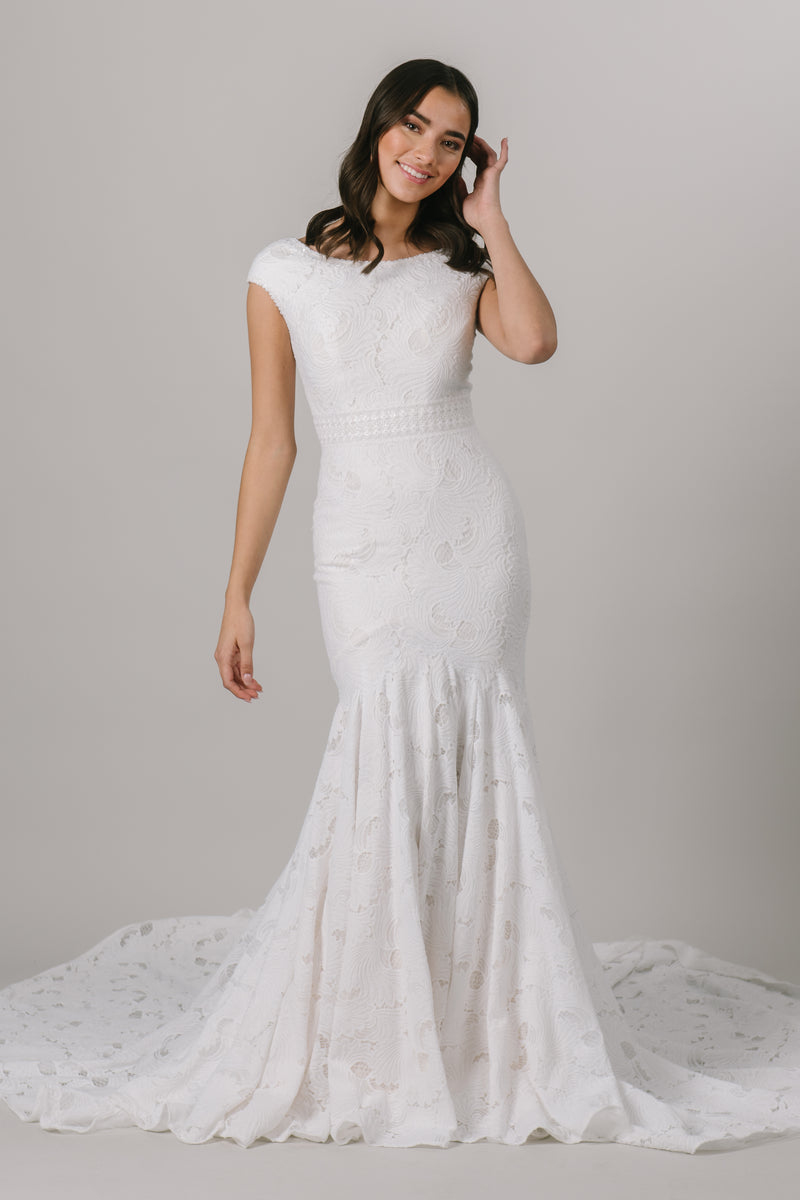 Fall in love with lace all over again! This stunning modest wedding dress features a sophisticated lace pattern, flattering fit-and-flare silhouette and an accentuated waistband that everyone loves!   Shown in Sand/Ivory.