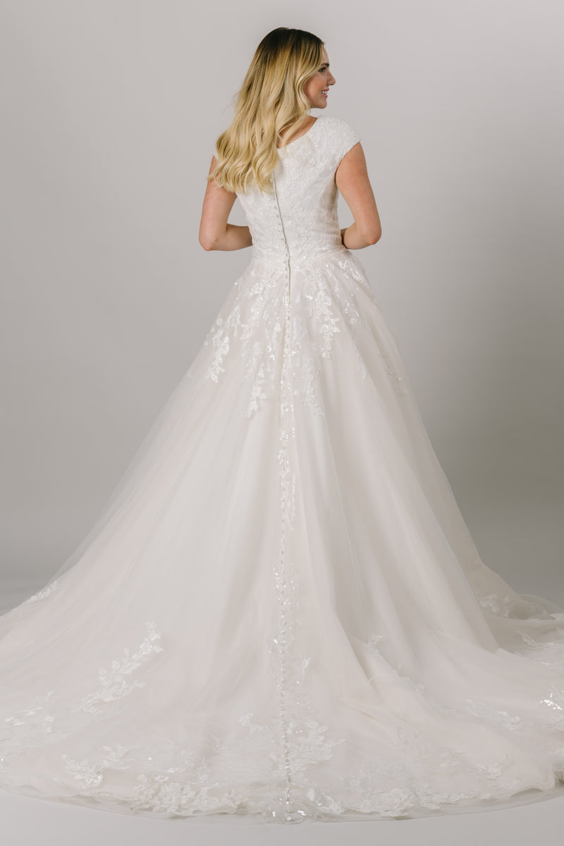 This modest ballgown wedding dress features a flattering fit and gorgeous sparkly floral lace throughout the bodice and trickling down the skirt. It has a soft v-neck and buttons down the back! Available in Ivory and Ivory/Champagne (pictured).  Style Love: Appliques from the top and bottom meet at the middle of the skirt! From a bridal shop in downtown Salt Lake City.
