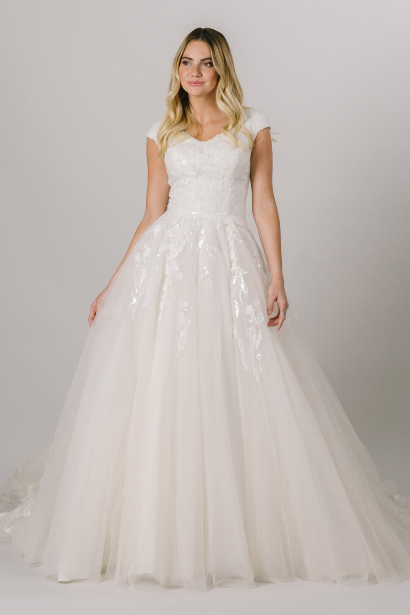 This modest ballgown wedding dress features a flattering fit and gorgeous sparkly floral lace throughout the bodice and trickling down the skirt. It has a soft v-neck and buttons down the back! Available in Ivory and Ivory/Champagne (pictured).  Style Love: Appliques from the top and bottom meet at the middle of the skirt!