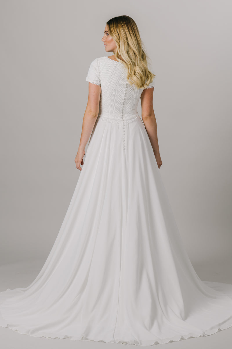 This a-line modest wedding dress features a scoop neck lace bodice with short sleeves. We absolutely love the embroidered detailing around the neckline and sleeves. Style Love: This dress is part of our brand new, exclusive LatterDayBride wedding dress collection. From a bridal shop, located in downtown SLC, Utah.