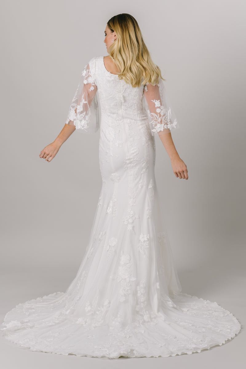 This unique modest wedding gown is like nothing you've seen! It features a v-neckline, fitted silhouette, and gorgeous flowery lace. This gown provides such an amazing fit with details you'll love! Available in Ivory and Ivory/DecoGold. From a bridal shop in downtown Salt Lake City called LatterDayBride.