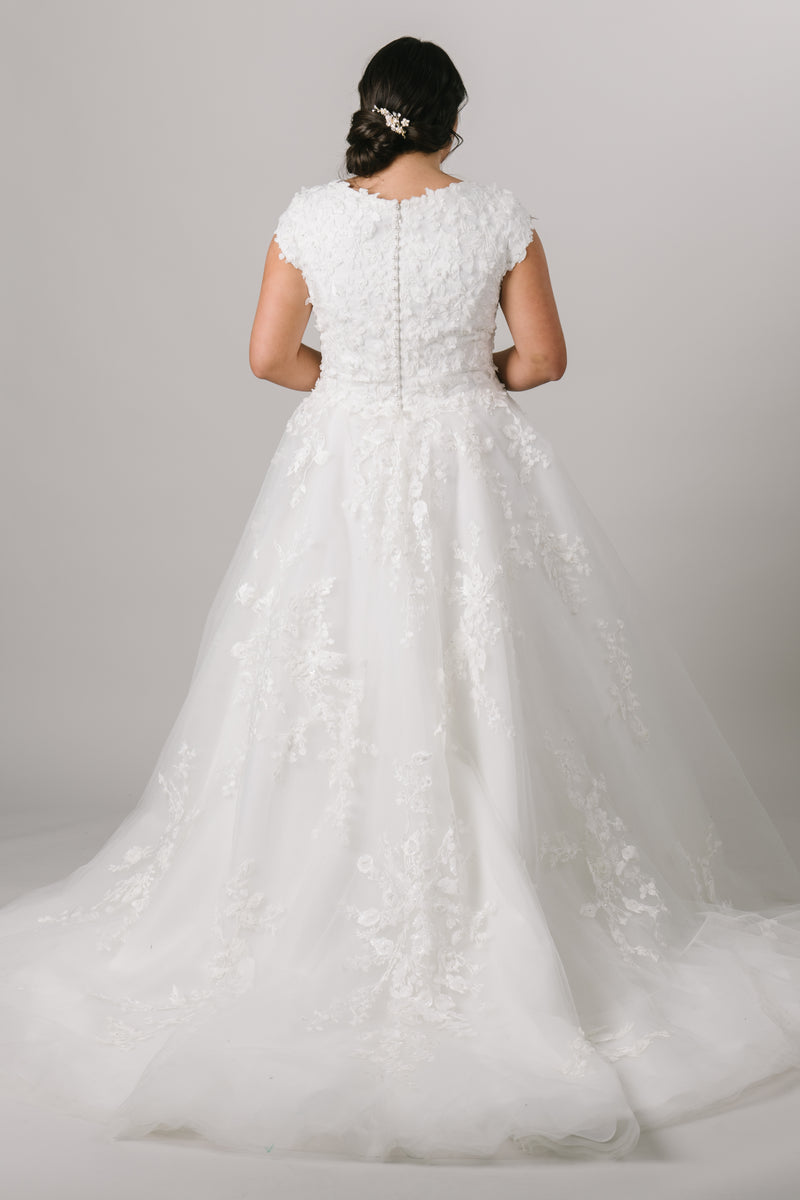 Bold and soft, this plus size modest ballgown wedding dress features a breathtaking sweetheart neckline and off-shoulder sleeves, delicately covered in blooming 3D floral lace. Available in White/White/White, Champagne/Nude/Ivory, Ivory/Ivory/Ivory, Silver Blush/Nude/Ivory (as pictured).  Silver Blush/Nude/Ivory sample available in store.