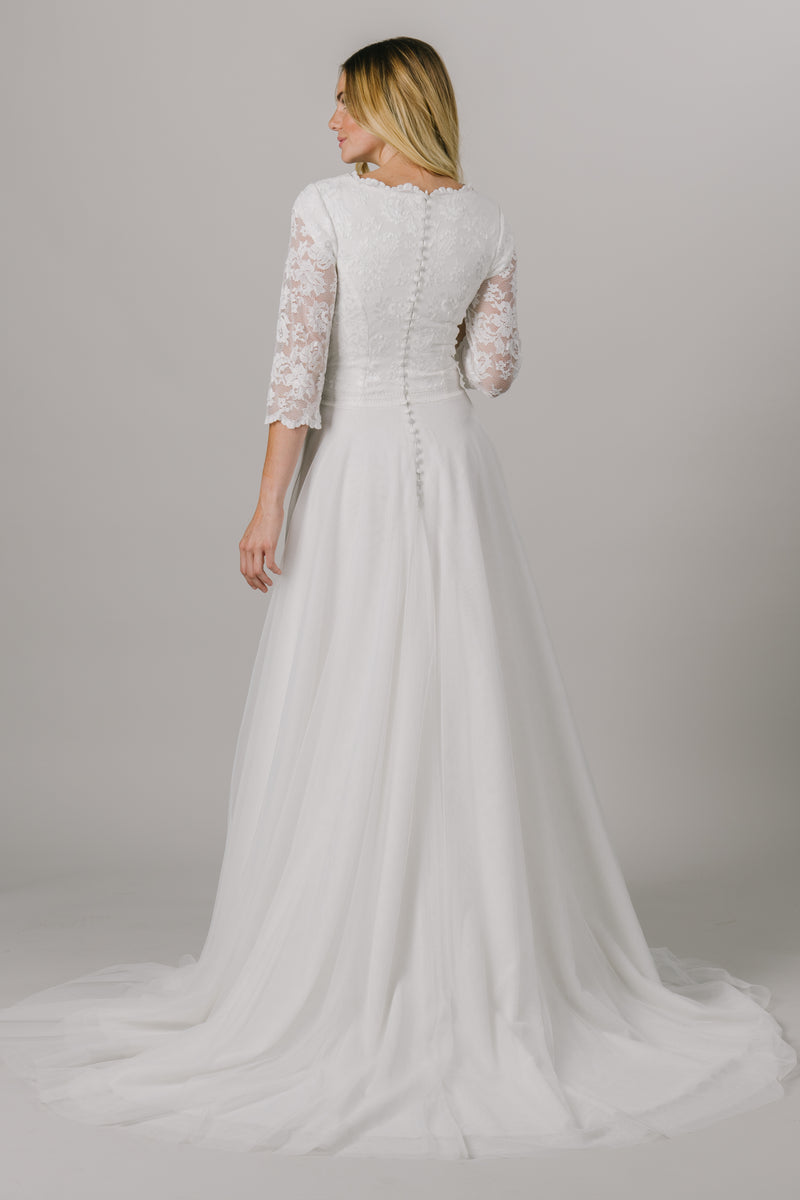 This a-line modest wedding dress is features a dainty lace bodice with 3/4 illusion sleeves. This gown has a scoop neck with small ruffles and an embroidered belt that is unbelievably flattering on the waist. Available in Ivory and Ivory/Cappuccino.  Style Love: This dress is part of our brand new, exclusive LatterDayBride wedding dress collection. The back view of the dress from a bridal store in SLC, Utah.