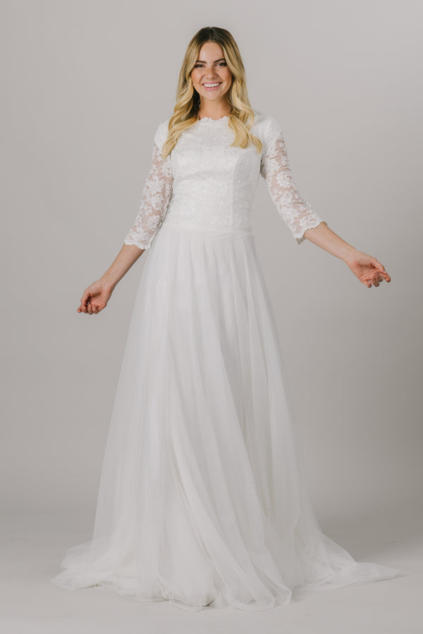 This a-line modest wedding dress is features a dainty lace bodice with 3/4 illusion sleeves. This gown has a scoop neck with small ruffles and an embroidered belt that is unbelievably flattering on the waist. Available in Ivory and Ivory/Cappuccino.  Style Love: This dress is part of our brand new, exclusive LatterDayBride wedding dress collection.