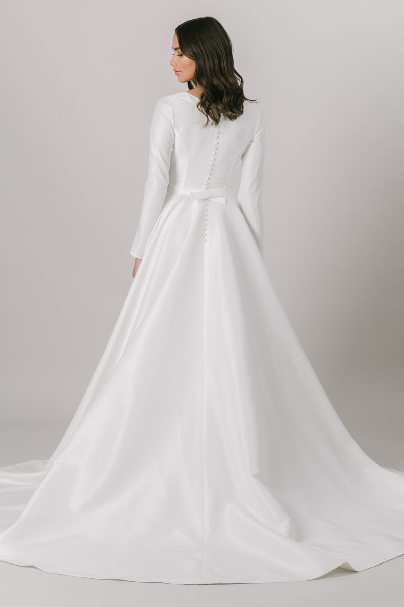 As the epitome of class and elegance, this modest wedding dress features a flattering ballgown fit with long sleeves and a v-neckline. And don't forget about the pockets! From a bridal shop in Salt Lake City called LatterDayBride.