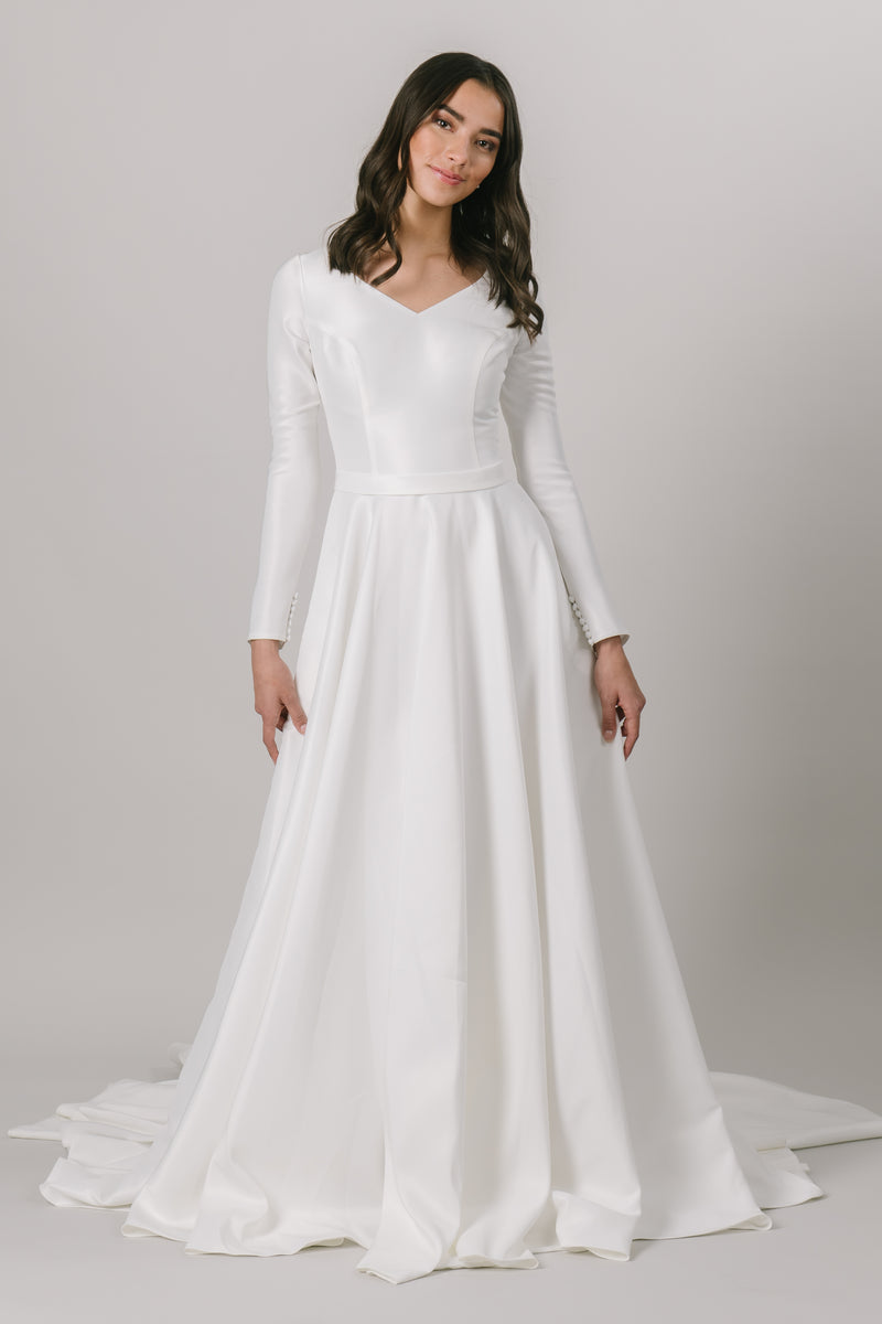 As the epitome of class and elegance, this modest wedding dress features a flattering ballgown fit with long sleeves and a v-neckline. And don't forget about the pockets!   Style Love: This dress is part of our brand new, exclusive LatterDayBride wedding dress collection.