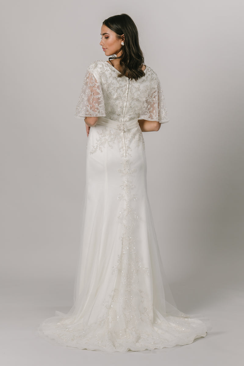 The back of a beaded A-line wedding dress with beaded flutter sleeves, from a bridal shop in salt lake city, utah.