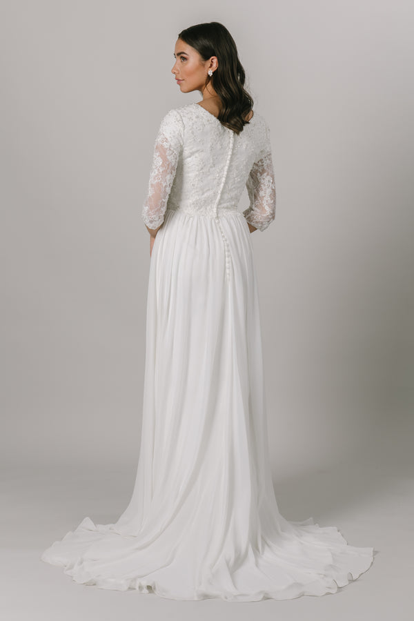 This modest wedding dress has a vintage chic vibe to it and we love it! It features a dazzling dress features lace illusion almost long sleeves, a high illusion neckline, and a flowy chiffon skirt.   Style Love: This gown is the perfect blend between simple and sparkly! From a bridal store in downtown SLC, Utah.