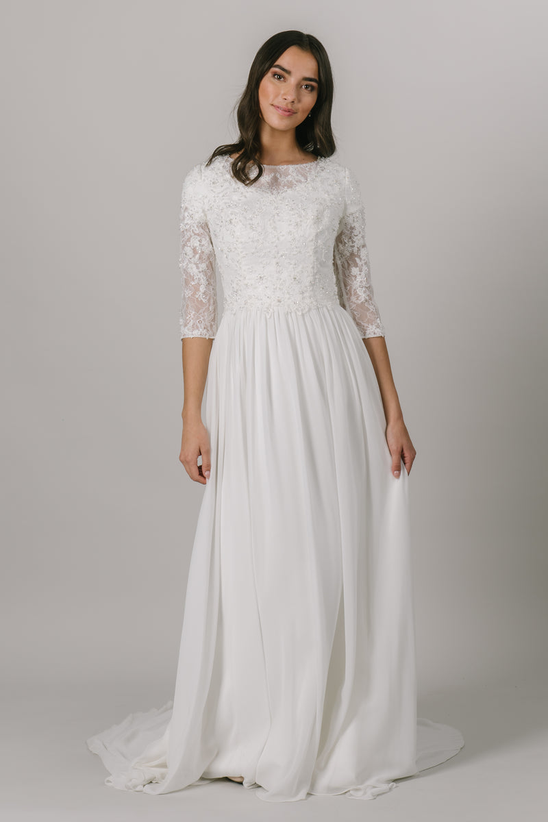 This modest wedding dress has a vintage chic vibe to it and we love it! It features a dazzling dress features lace illusion almost long sleeves, a high illusion neckline, and a flowy chiffon skirt.   Style Love: This gown is the perfect blend between simple and sparkly!