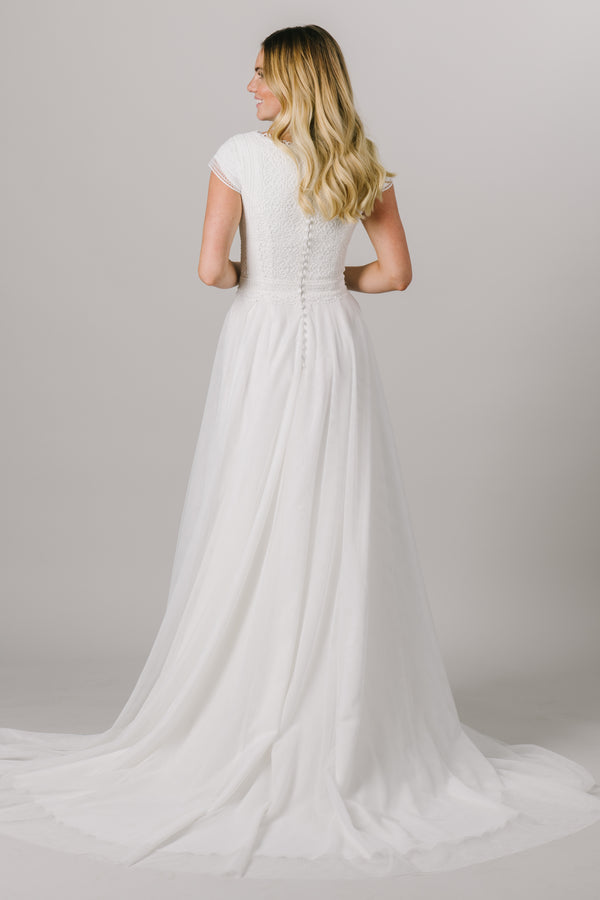 This a-line, modest wedding dress features a flattering lace bodice with delicate sleeves and a lightweight skirt. A fun scoop neck is the perfect cherry on top of this classic wedding gown. Style Love: This dress is part of our brand new, exclusive LatterDayBride wedding dress collection. From a bridal shop in Salt Lake City called LatterDayBride.