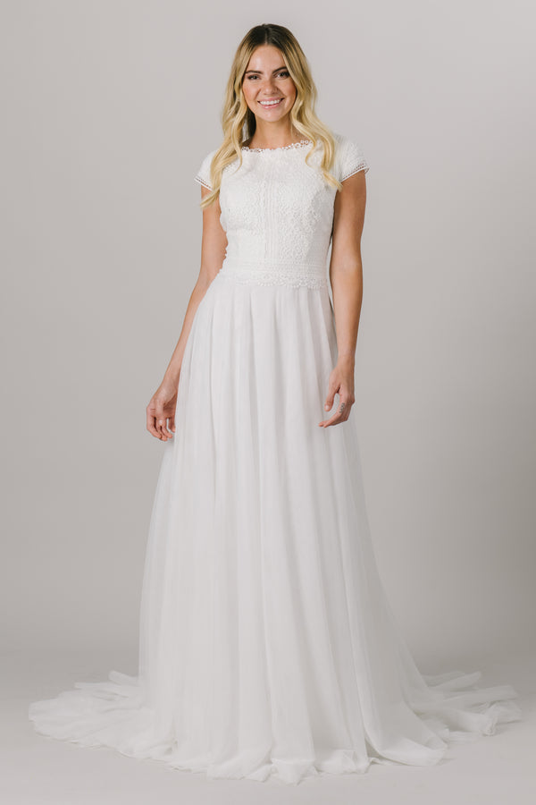 This a-line, modest wedding dress features a flattering lace bodice with delicate sleeves and a lightweight skirt. A fun scoop neck is the perfect cherry on top of this classic wedding gown. Style Love: This dress is part of our brand new, exclusive LatterDayBride wedding dress collection.
