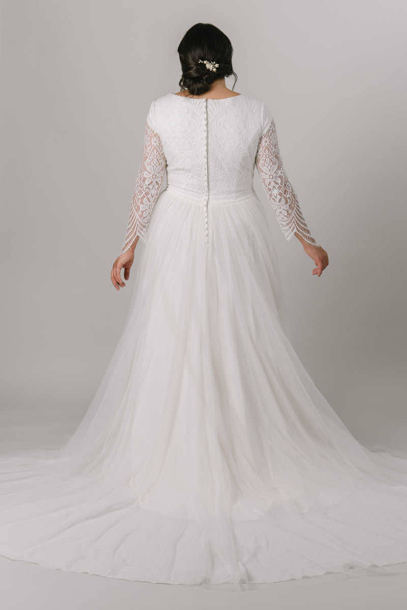 This modest wedding dress has a laced bodice with quarter length illusion sleeves. The soft a-line tulle connected with an embroidered empire waistline. This gown speaks elegance.   Style Love: This unique dress features a quarter length sleeve with illusion lace. Not many dresses share that aspect!   Dress available only in Sand/Ivory  Sand/Ivory sample available in the store. (Pictured) Plus size available in store.  From a bridal store in downtown SLC, Utah.