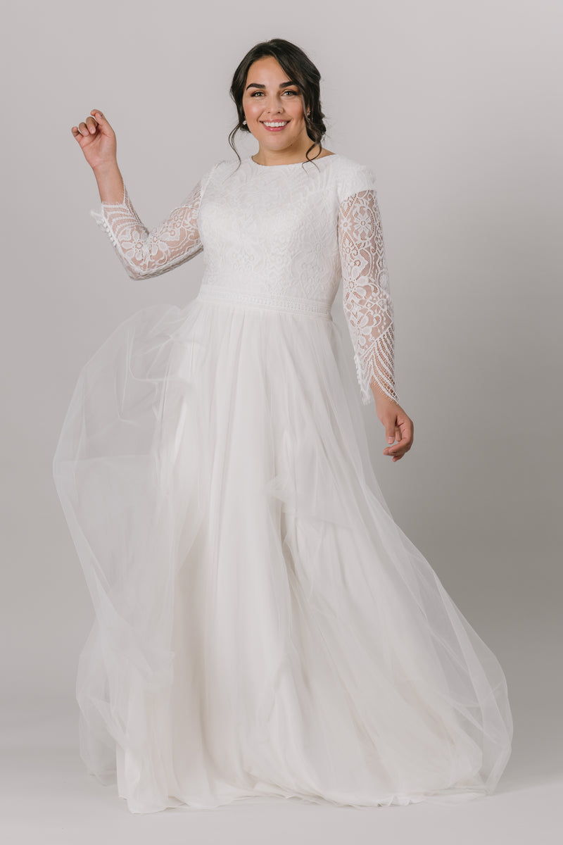 This modest wedding dress has a laced bodice with quarter length illusion sleeves. The soft a-line tulle connected with an embroidered empire waistline. This gown speaks elegance.   Style Love: This unique dress features a quarter length sleeve with illusion lace. Not many dresses share that aspect!   Dress available only in Sand/Ivory  Sand/Ivory sample available in the store. (Pictured) Plus size available in store.