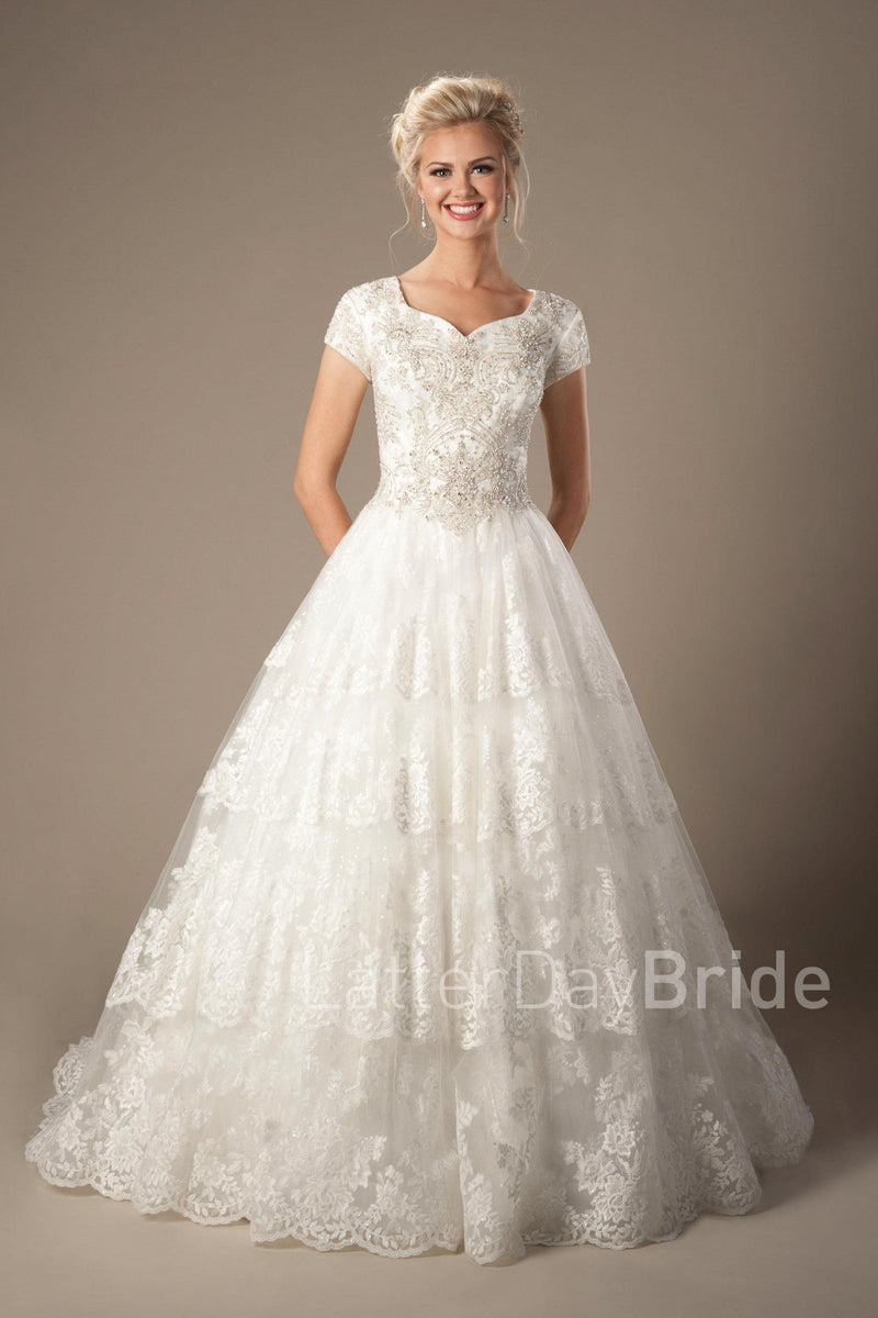 modest bridal dress features a lovely sweetheart neckline and a dazzling beaded bodice complimented by a full skirt with tiered lace, modest wedding gown salt lake city, front view