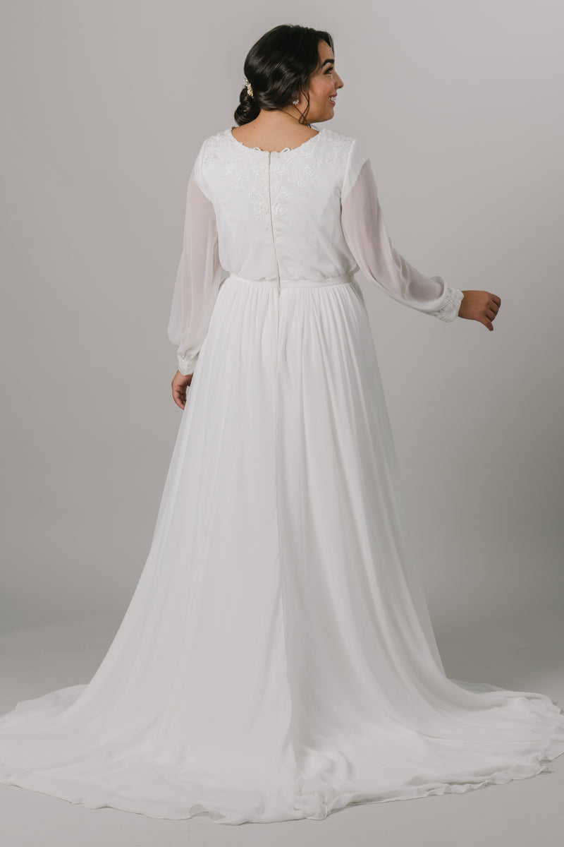 The back of a plus size version long-sleeve modest wedding dress features a v-neckline, bishop sleeves, and an a-line fit that flatters every figure.   Style Love: Gorgeous shimmering lace around the neckline and sleeve cuffs!