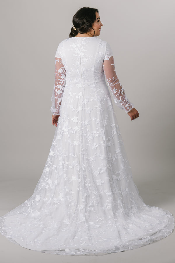 This long-sleeve modest wedding dress features a hand-embroidered lace pattern with an A-line skirt and a prairie chic feel. Plus size available in store.  Style Love: The soft puff of the sleeve is undeniably darling, and we are smitten with the flow of the skirt. Totally twirlable! From a bridal shop in downtown SLC,Utah.