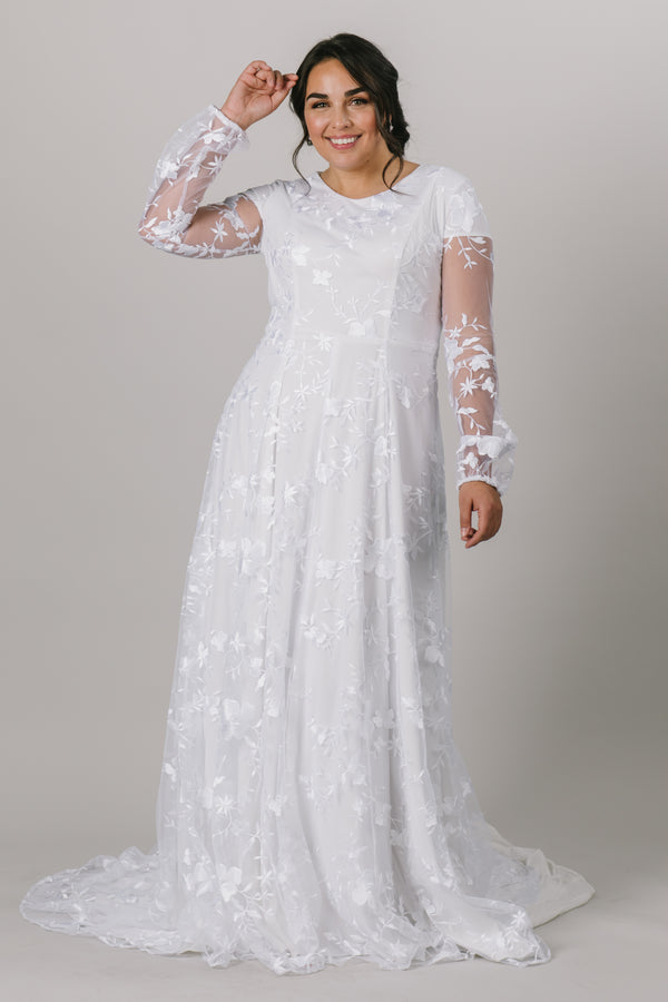 This long-sleeve modest wedding dress features a hand-embroidered lace pattern with an A-line skirt and a prairie chic feel. Plus size available in store.  Style Love: The soft puff of the sleeve is undeniably darling, and we are smitten with the flow of the skirt. Totally twirlable!