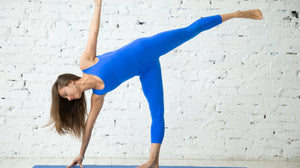 Lady performing yoga posture ardha chandrasana or half moon pose