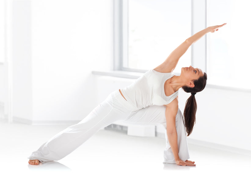 Attractive woman performing yoga pose extended side angle.