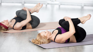 two ladies practicing yoga doing the yoga posture apanasana the wind relieving pose