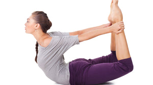 Lady practicing the yoga posture dhanurasana - the bow pose