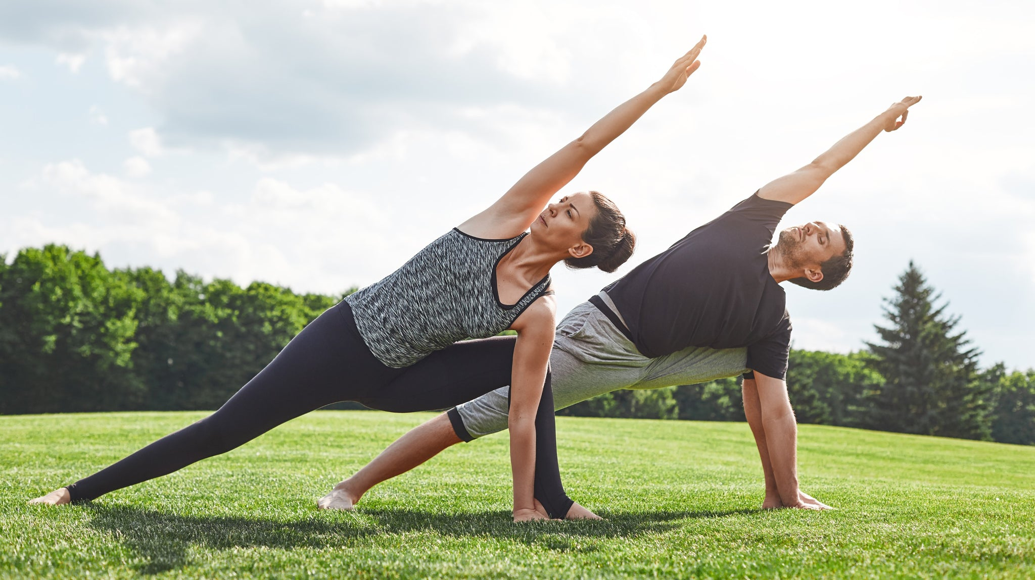 Two people in a park performing the yoga pose parsvokanasana - extended side angle