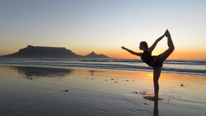 Young woman doing najarasana dancer pose on a beach