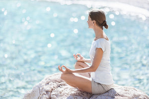 Young Woman meditating looking out to sea