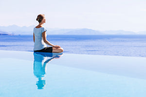 Lady sitting crossed legged looking out to sea in a yoga pose